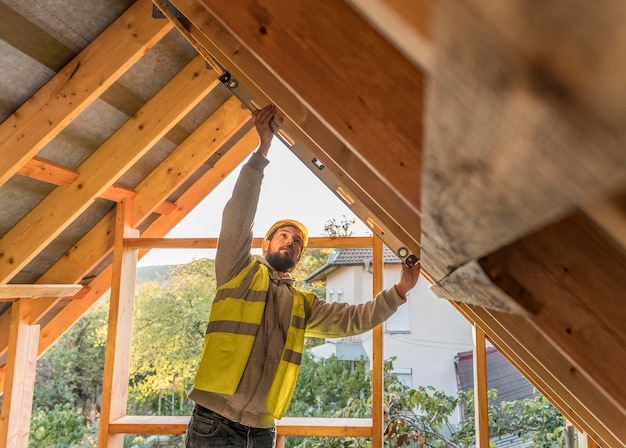 Carpenter man working on a roof Free Photo
