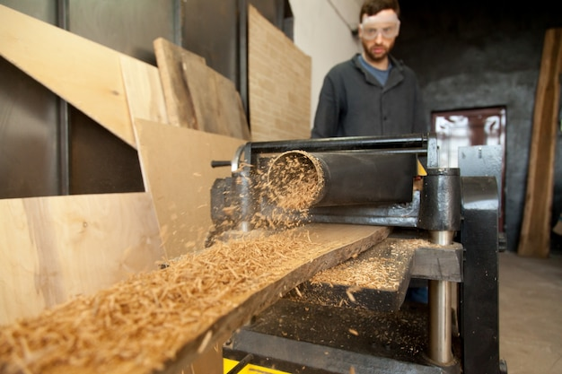 Carpenter operating stationary power planer, processing wooden plank, making sawdust Free Photo