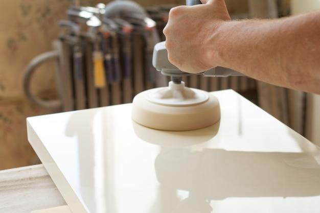 Карпентер полирует поверхность фасада перед сборкой мебели Premium Фотографии