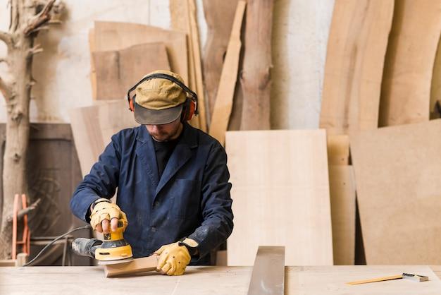 Carpenter polishes wooden board with a random orbit sander in the workshop Premium Photo