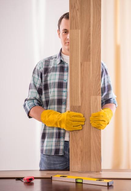Carpenter in rubber gloves holding wooden planks. Premium Photo