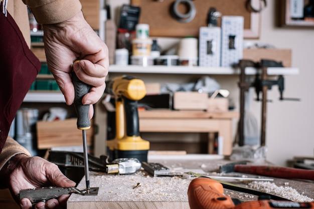 Carpenter screwing a hinge to a board with a screwdriver Premium Photo