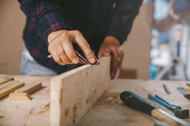Карпентер использует шлифованную бумагу по дереву. строительная промышленность, работа по дому сделай сам Premium Фотографии