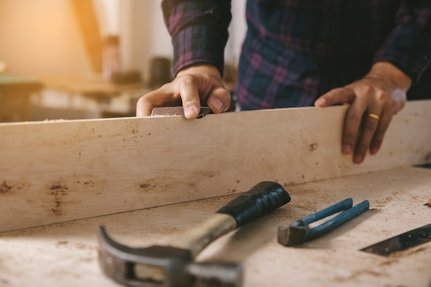 Carpenter uses sandedpaper on wood.construction industry, housework do it yourself. Premium Photo