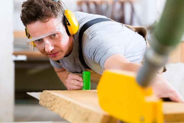 Carpenter using electric saw in carpentry Premium Photo
