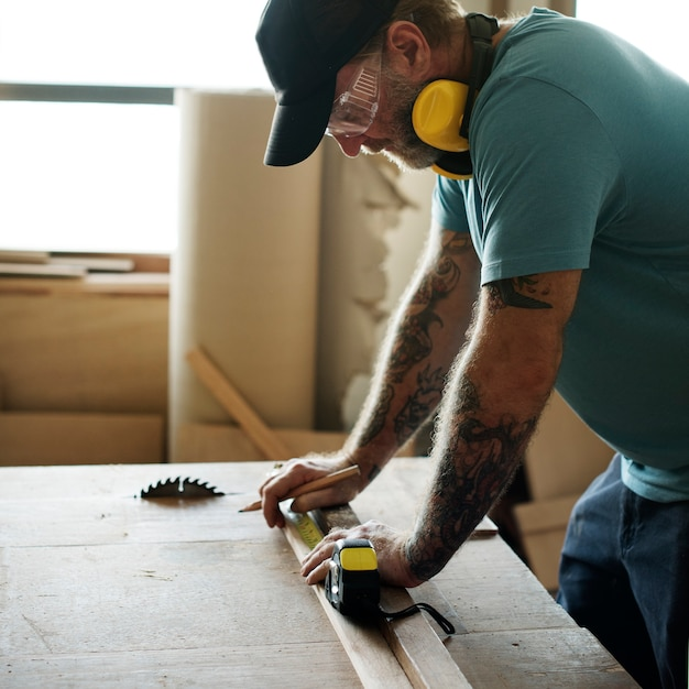 Carpenter using pencil and measurement tape on wood Free Photo