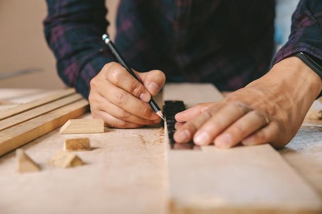 Плотник с меткой карандаша и правителя на деревянной доске на таблице. строительная индустрия, работа по дому сделай сам. Premium Фотографии