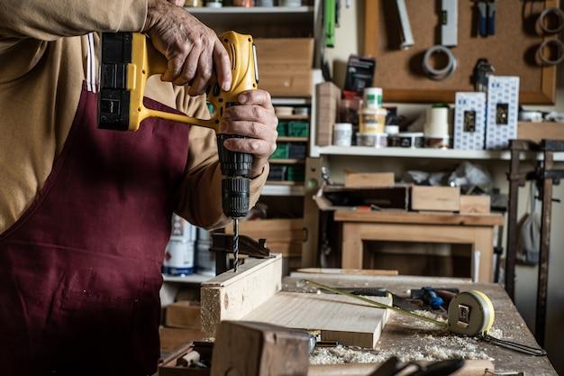 Плотник с желтым сверлом проделывает отверстие на борту деревянного сверла Premium Фотографии