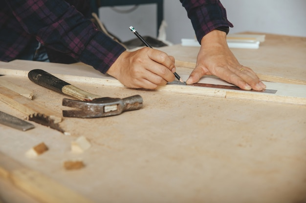 Carpenter with a pencil and ruler mark on wooden board on table. construction industry, housework do it yourself. Premium Photo