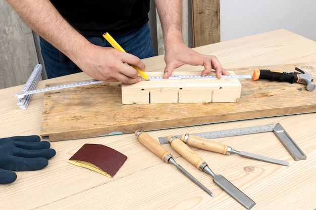 Carpenter worker creating home decoration from wood in his workshop Free Photo