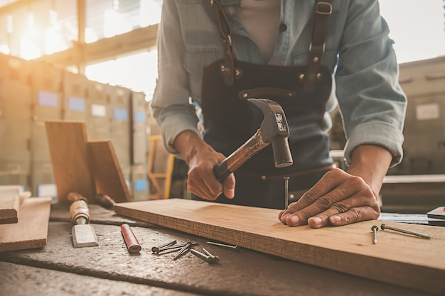 Carpenter working with equipment on wooden table in carpentry shop. Premium Photo