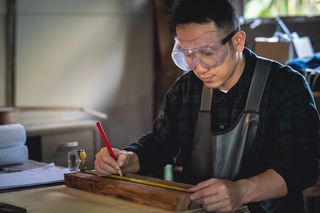 Carpenter working on wood in carpentry shop. the man works in a carpentry shop Premium Photo