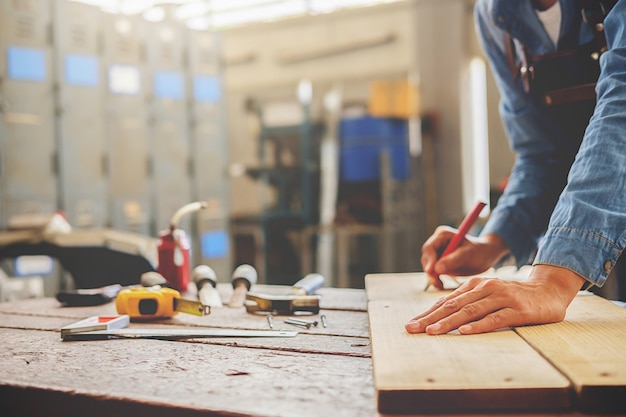 Carpenter working on woodworking machines in carpentry ...