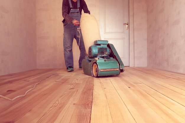 Carpenter works by electric grinding wood machine in a room Premium Photo