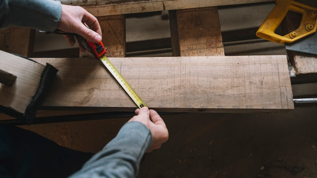 Carpentry concept with man measuring Free Photo