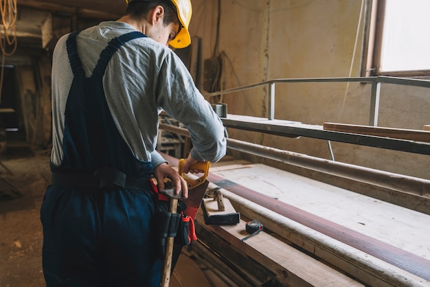 Carpentry concept with man working on wood Free Photo