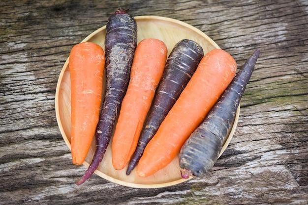 Морковь и фиолетовая морковь на подносе, свежая морковь для приготовления вегетарианских блюд на деревянном столе на кухне Premium Фотографии