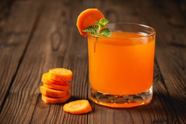 Carrot juice in glass on wooden table. Free Photo