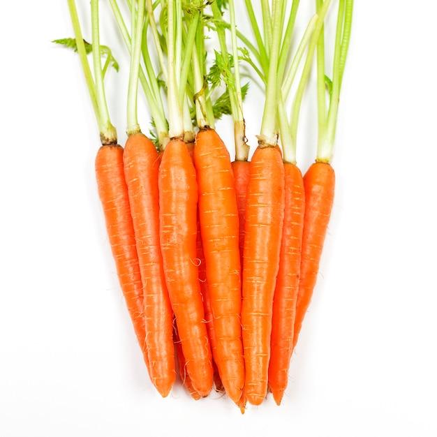 白い背景で隔離の葉とニンジン野菜 Premium写真