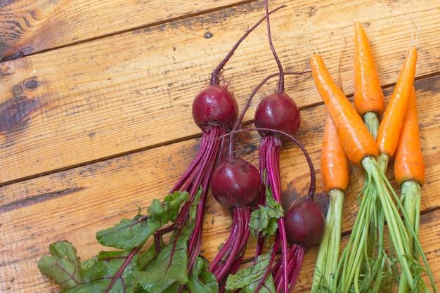 Морковь и свекла с стеблями и листьями. Premium Фотографии