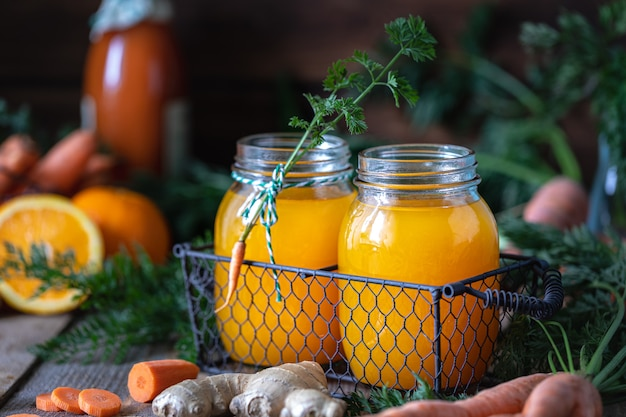 Carrots and carrot juice with orange ginger in a glass jar in a metal basket Premium Photo