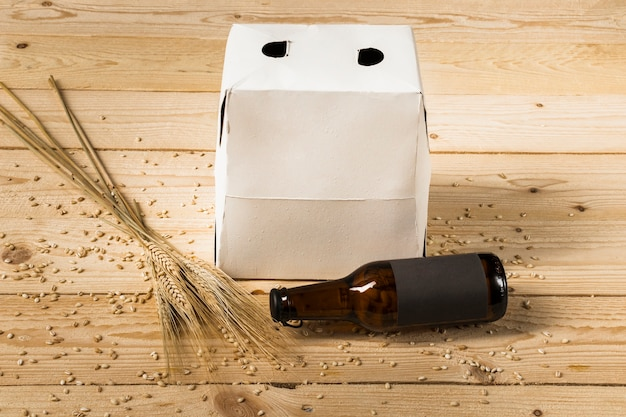 Carton box; beer bottle and ears of wheat on wooden surface Free Photo