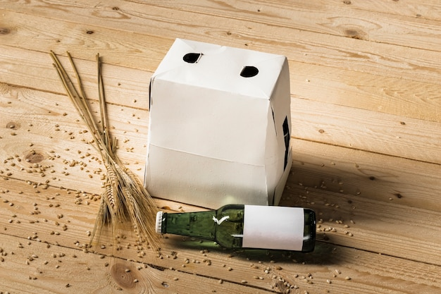 Carton box; green beer bottle and ears of wheat on wooden plank Free Photo