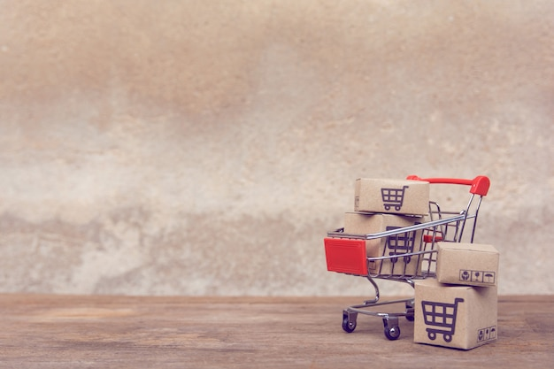 Cartons or paper boxes in shopping cart on brown wood table. Premium Photo