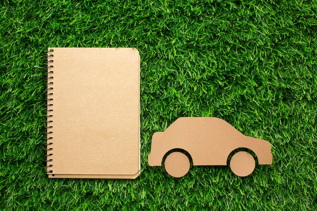 Cartoon car and notebook in grass Free Photo
