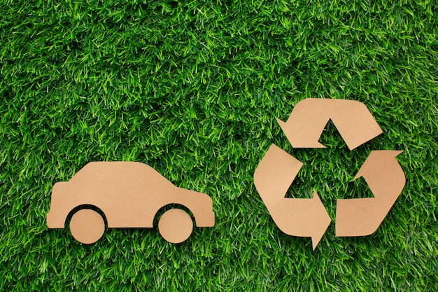 Cartoon car and recycle sign in grass Free Photo