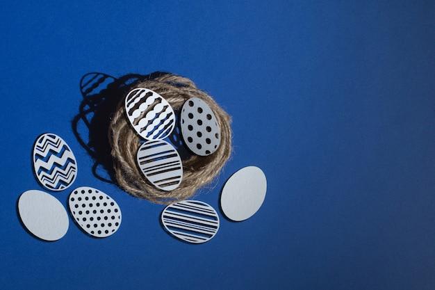 Резные пасхальные яйца в джутовом гнезде на классическом синем фоне, цвет 2020 classic blue pantone Premium Фотографии