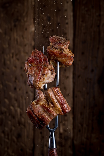 Carving fork with pieces of steak on rustic background Premium Photo