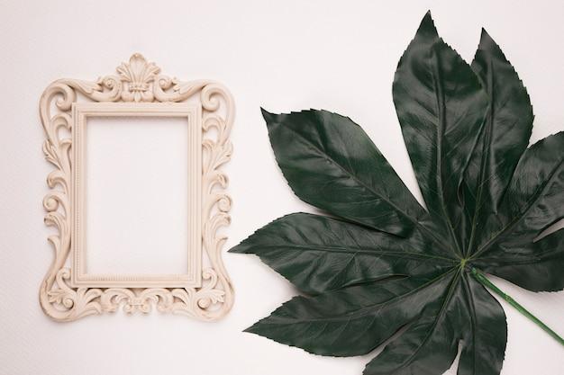 Carving rectangular wooden frame on green single leaf against backdrop Free Photo