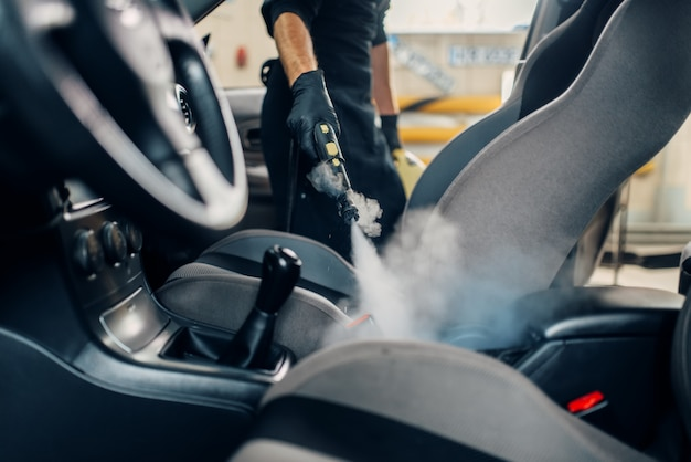 Carwash, worker cleans seats with steam cleaner Premium Photo
