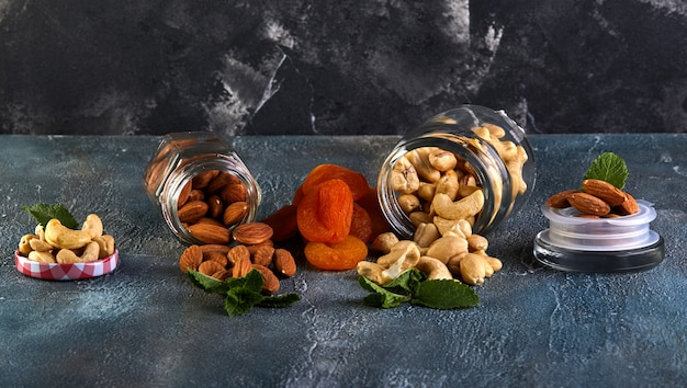 Cashew almonds spill out of transparent cans, dried apricots lie between them Premium Photo