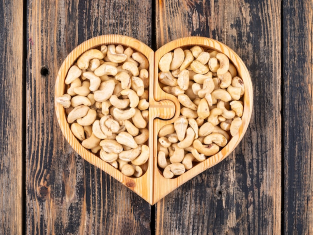 Cashew in a heart shaped wooden plate top view on a wooden table Free Photo