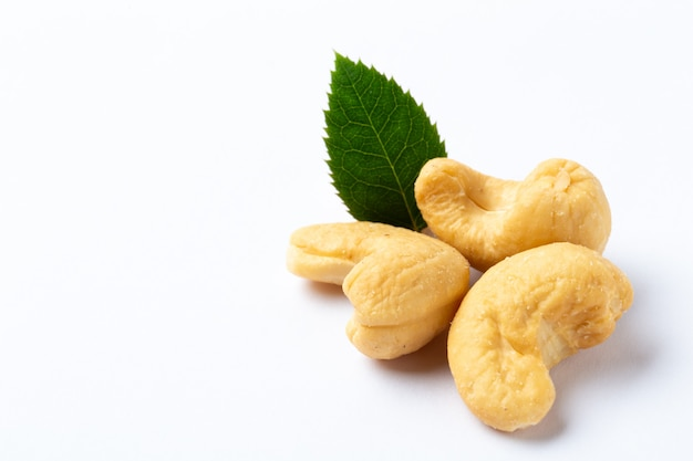 Cashew nuts with a green leaf on white background Premium Photo