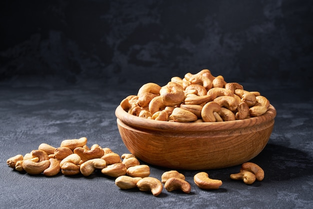 Cashew nuts in wooden bowl on black, close-up Premium Photo