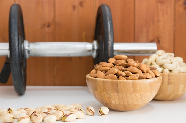 Cashews and almonds with a dumbbell behind Premium Photo