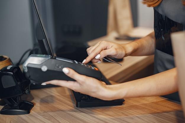 キャッシャーはターミナルを介してカードで支払いますキャッシャーはターミナルを介してカードで支払います。 無料写真