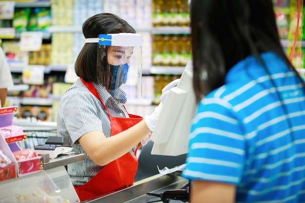 Cashier or supermarket staff in medical protective mask and face shield working at supermarket. Premium Photo