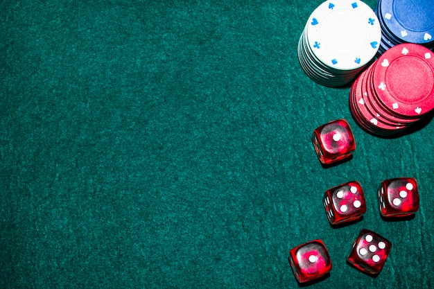 Casino chips and dice on green table Free Photo