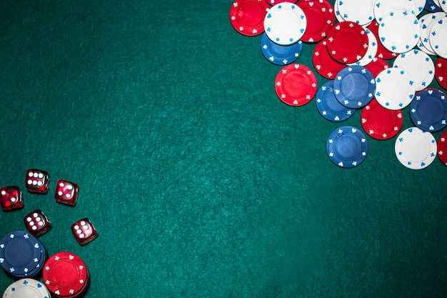 Premium Photo | Casino chips and red dices on green poker backdrop