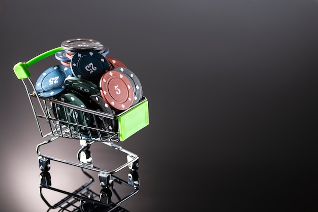 Casino chips in a shopping basket on a dark background with reflection Premium Photo