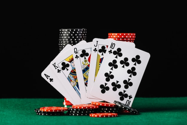 Premium Photo | Casino chips stack and royal flush playing card on green  poker table