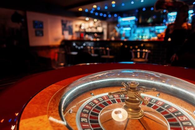 バーの木製の金色のテーブルとカジノのルーレット Premium写真