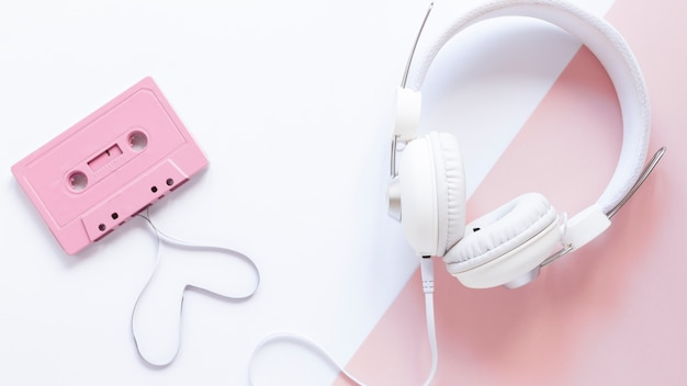 Cassette and earphones on white and pink background Free Photo