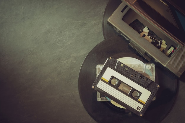 Cassette player and platter record on cement floor Premium Photo