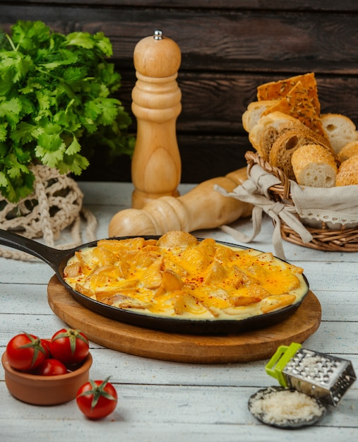 Cast iron pan of fried potatoes with eggs served with bread and cheese Free Photo