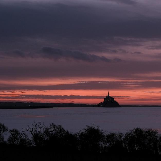 日没時の曇り空の下、海の前の城 無料写真